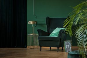 picture of a monochromatic color-coordinated living room with green walls and a green chair