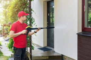 a professional painter power washing the outside of a house